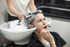 Femme choquée dans un salon de coiffure photographie stock