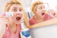 Femme choquée employant la brosse de nettoyage faciale images libres de droits