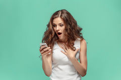 Femme choquée regardant le téléphone portable sur le fond vert Photographie stock libre de droits