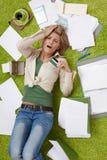 Femme choquée sur le plancher avec des factures Image libre de droits