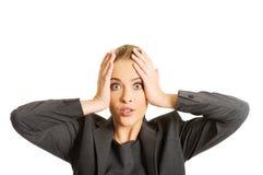 Femme choquée tenant des mains sur le menton Images stock