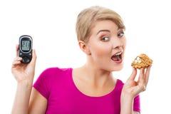 Femme choquée tenant le glucometer et le petit gâteau frais, niveau de mesure de sucre, concept de diabète Photographie stock