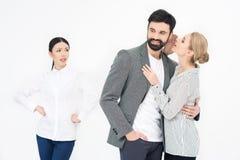 Femme chuchotant à l'homme avec l'ami jaloux tout près Image libre de droits