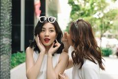 Femme chuchotant dans des ses oreilles d'amis Shoppi enthousiaste de deux amis Photos stock
