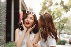 Femme chuchotant dans des ses oreilles d'amis Shoppi enthousiaste de deux amis Image stock