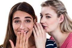 Femme chuchotant dans l'oreille d'ami Photo stock