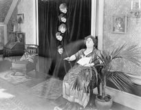 Femme cinq regardant une femme par derrière un rideau (toutes les personnes représentées ne sont pas plus long vivantes et aucun  Photographie stock