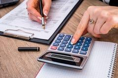 Femme classant la forme individuelle 1040 d'impôt sur le revenu photos libres de droits
