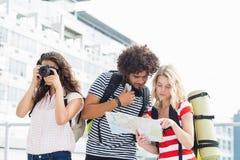 Femme cliquant sur la photo tandis que ses amis regardant la carte Image libre de droits