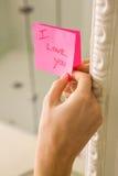 Femme collant je t'aime la note sur le miroir Photographie stock libre de droits
