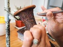 Femme collant les fils formés minuscules de cloisonne à un creati de cuivre de vase Images stock