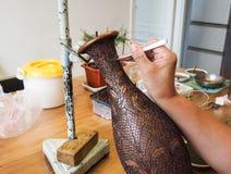 Femme collant les fils formés minuscules de cloisonne à un creati de cuivre de vase Photos libres de droits