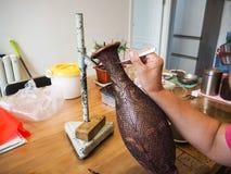 Femme collant les fils formés minuscules de cloisonne à un creati de cuivre de vase Image stock