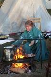Femme coloniale faisant cuire au-dessus d'un feu Image stock