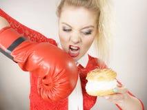 Femme combattant la nourriture gâtée, gâteau de boxe de souffle crème Photographie stock