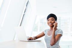 Femme comptable de jeune femme de sourire d'afro-américain à l'aide de l'ordinateur portable et du smartphone Photos libres de droits