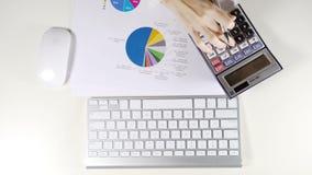 Femme comptable travaillant avec le document de calculatrice et de graphique sur le bureau blanc dans le bureau clips vidéos