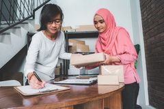 Femme comptant sur le paquet sur une étagère photographie stock