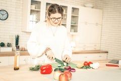 Femme concentrée en verres clairs coupant des concombres avec le couteau pointu photographie stock
