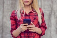 Femme concentrée et calme introduisant et recevant des messages sur son smartphone Le message de sms de lecture rapide d'influenc photos libres de droits