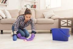 Femme concentrée polissant le plancher en bois photos stock