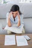 Femme concentrée vérifiant ses factures Photographie stock libre de droits