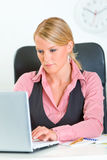 Femme concentrée d'affaires s'asseyant au bureau Photographie stock