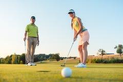 Femme concurrentielle regardant la boule de golf avec la déception photographie stock libre de droits