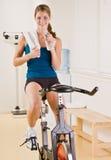 Femme conduisant la bicyclette stationnaire dans le club de santé Photographie stock