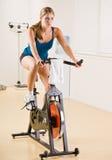 Femme conduisant la bicyclette stationnaire dans le club de santé Photo stock