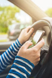 Femme conduisant la voiture et le message textuel sur le smartphone Photographie stock