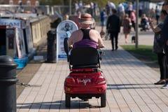 Femme conduisant le chapeau de port du soleil de scooter de mobilité Photo libre de droits