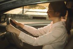 Femme conduisant son véhicule conducteur femelle tenant le volant image stock