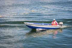 Femme conduisant un canot automobile dans le lac Titicaca, Pérou photo stock