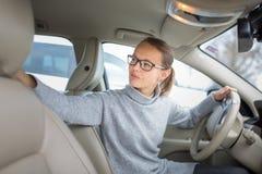 Femme conduisant un stationnement automobile, entrant à l'envers Image libre de droits