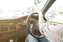 Femme conduisant une voiture dans la ville Photos stock