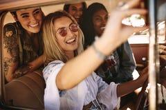 Femme conduisant une voiture et faisant le selfie avec des amis Photo libre de droits