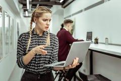 Femme confuse avec deux tresses semblant déroutées tout en traitant des aspects de travail photos stock