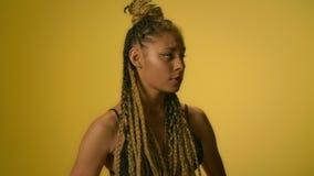 Femme confuse avec la main de tournoiement de coiffure Afro sur le fond jaune dans le studio clips vidéos