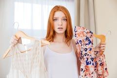Femme confuse choisissant entre deux robes Image libre de droits