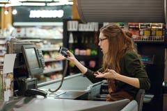 Femme confuse de caissier sur l'espace de travail dans le supermarché Photographie stock