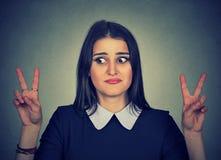 Femme confuse douteuse avec le signe de victoire photos libres de droits