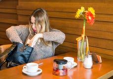 Femme confuse recherchant quelque chose dans son sac Images stock