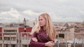 Femme congelée dans le froid de sensation de veste en cuir tout en se tenant sur le toit dans le vent clips vidéos