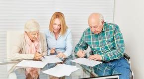 Femme conseillant le vieillard pour des finances photographie stock libre de droits