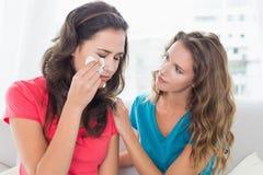 Femme consolant un ami féminin pleurant à la maison Photos libres de droits