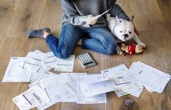 Femme contrôlant la dette se reposant près du chien photos stock