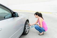 Femme contrôlant des pneus Photos stock