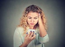 Femme contrariée, pissée par ce qu'elle a vu à son téléphone portable Image stock