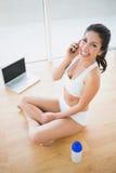 Femme convenable appelant avec le smartphone et souriant à l'appareil-photo Images stock